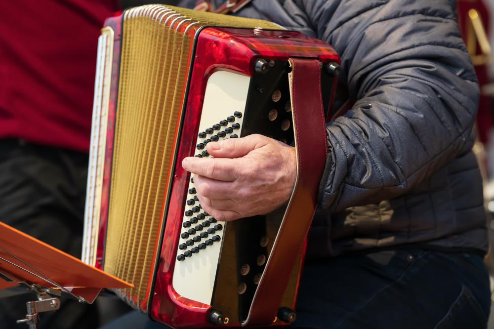 ein Harmonikaspieler greift in die Tasten - Dunkel Harfe Musikinstrument Person Stockfoto braun